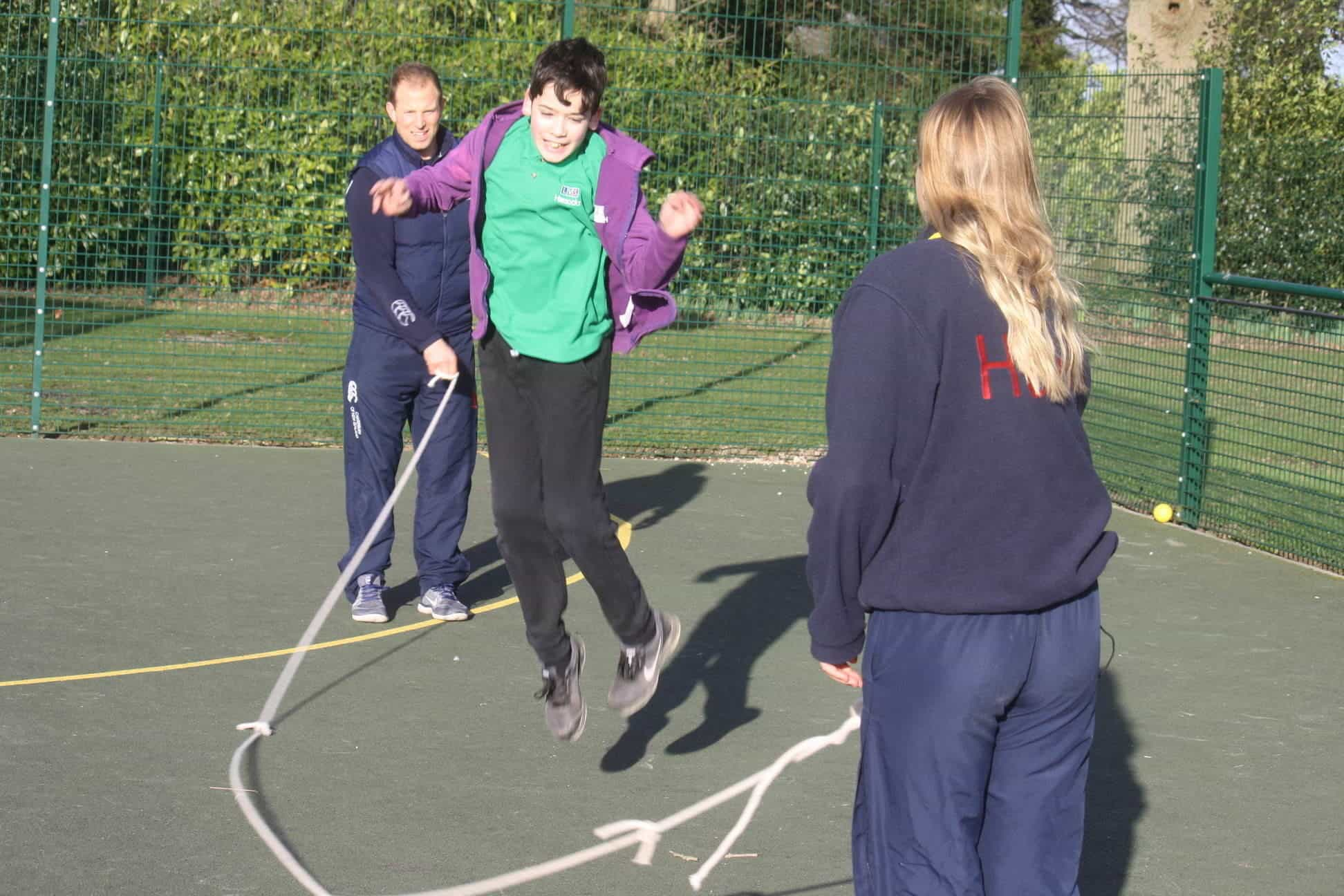boy pupil tries out skipping with the support of role models