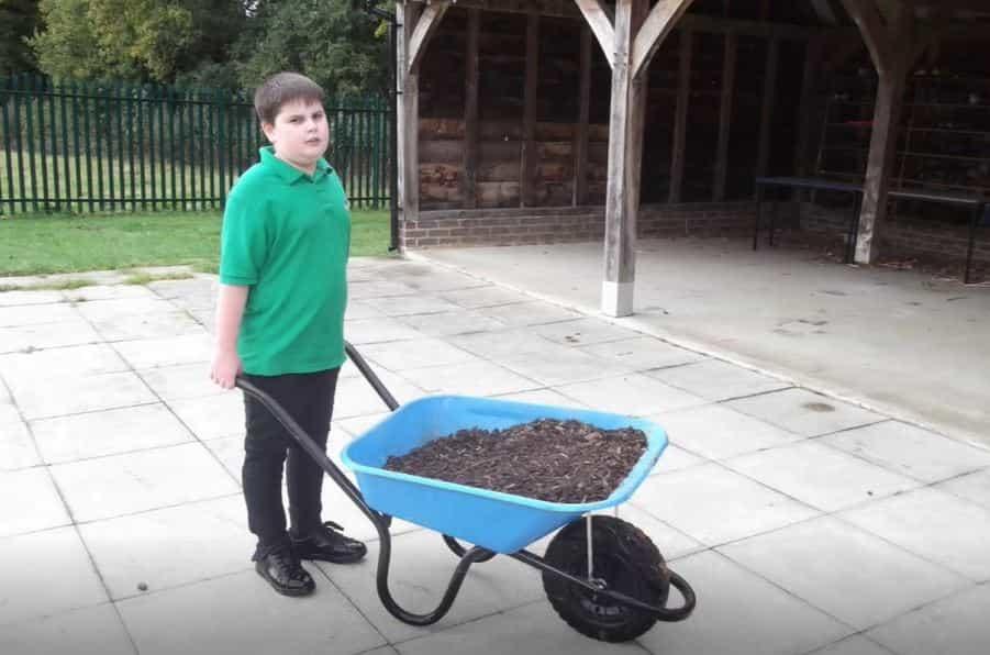 Young student pushing blue wheel barrow